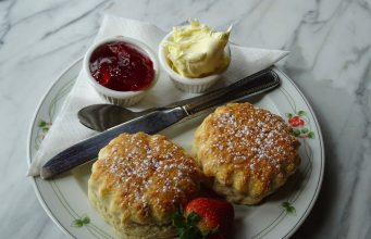 Zwei Scones mit Clotted Cream und erdbeermarmelade und Erdbeere