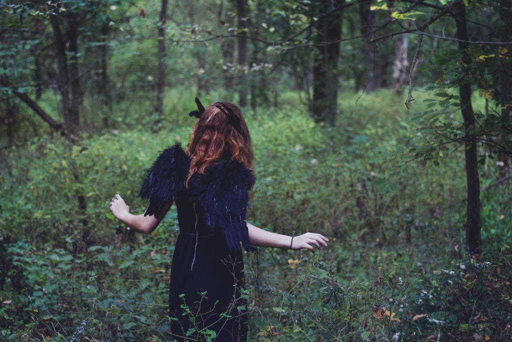 Mädchen mit blauen Flügeln irrt im Wald umher