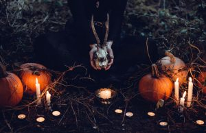 hands holding a skull with candles and pumpkin