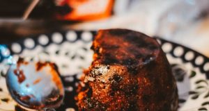 Halb aufgegessener Plum Pudding auf buntem Teller mit Löffel