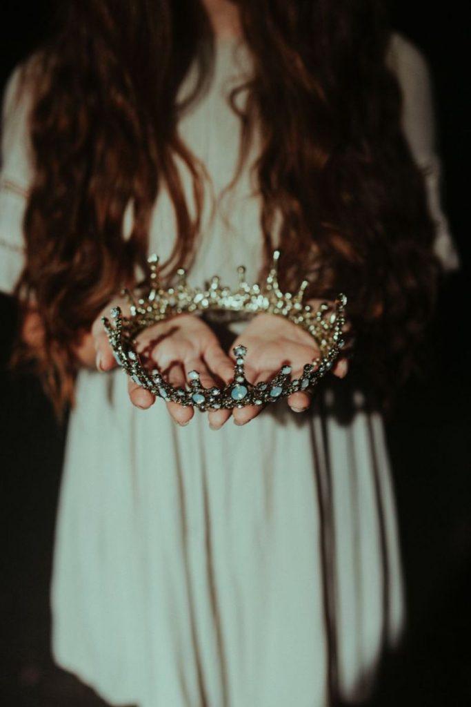 Langhaariges Mädchen im weißen Kleid trägt Krone.