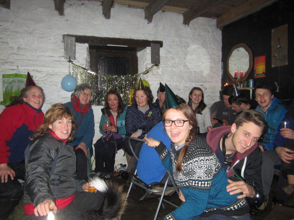 Silvester in den schottischen Highlands. 14 Personen in Mountain Boothy am Silvesterfeiern mit Partyhütchen