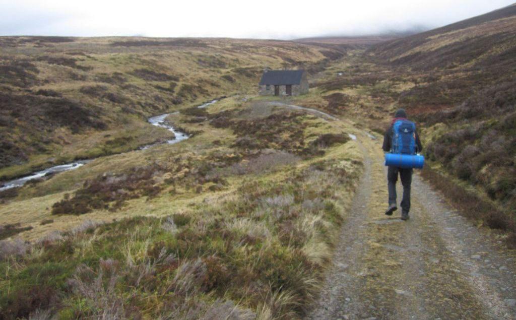 Silvester in den schottischen Highlands. Mountain Boothy / Berghütte in der Ferne, Wanderpfad neben Bachlauf durch die Munros