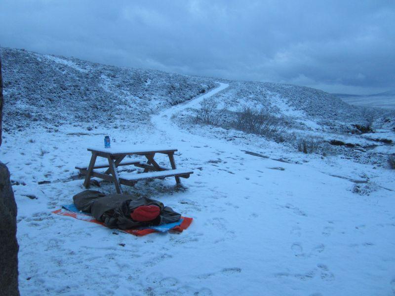 Silvester in den schottischen Highlands. Verschneiter Platz vor der Berghütte mit Bivy Bag im Schnee