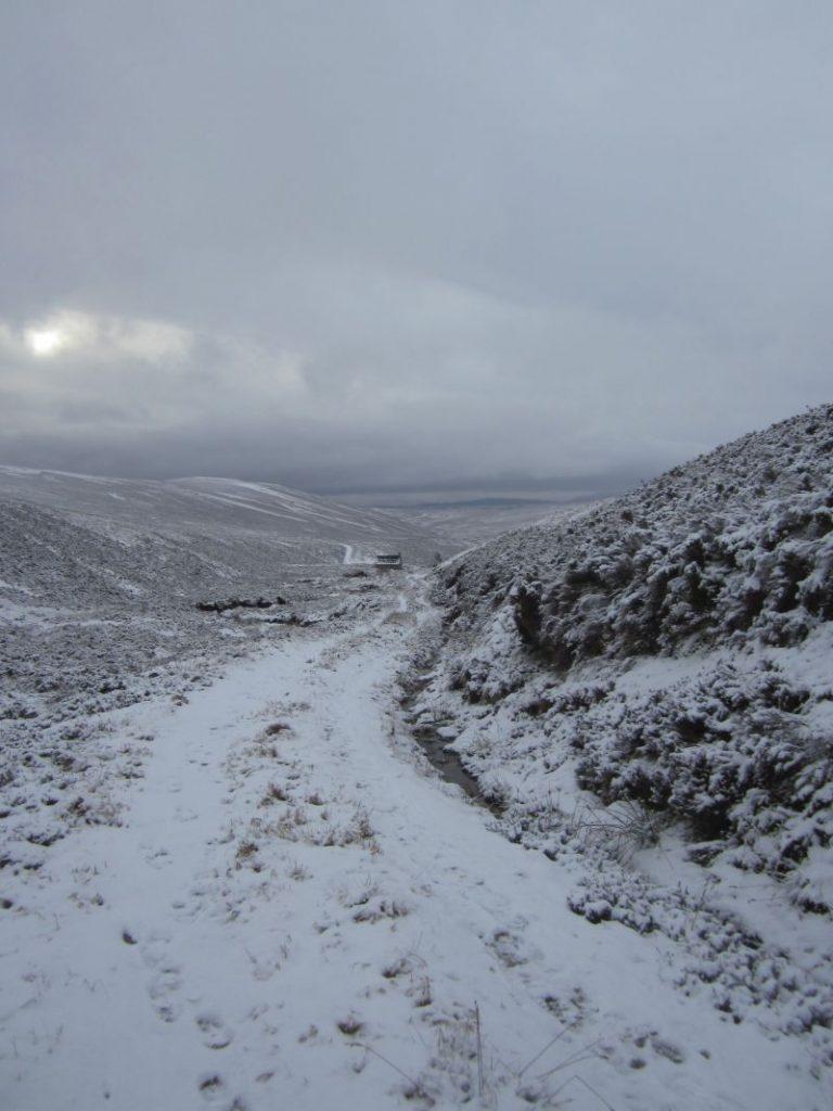 Silvester in den schottischen Highlands. Verschneiter Wanderweg zu der Berghütte