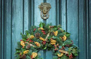 weihnachtlicher Türkranz auf petrolfarbener Holztür.