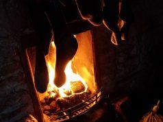 Silvester in den schottischen Highlands. Offenes Kaminfeuer mit Socken zum Trocknen davor