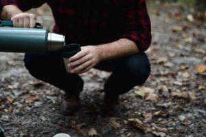 Mann in der Hocke gießt aus einer Thermoskanne etwas in den Becher