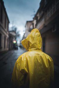 Person von hinten im gelben Regenmantel mit hochgezogener Kapuze