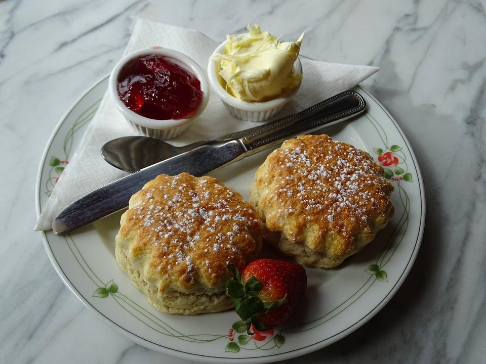 Zwei Scones auf weißem Teller mit Clotted Cream und Erdbeermarmelade und einer Erdbeere und Teebesteck