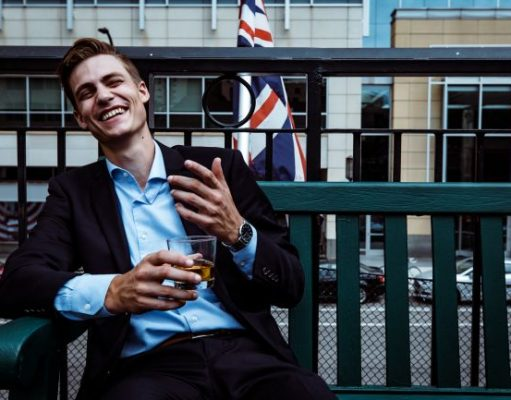 English man sitting on a bench in fron of the English flag with a glass in his hand