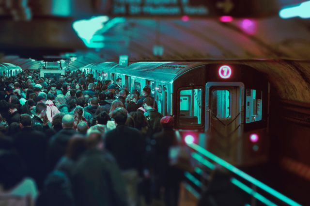 Völlig überfüllter Bahnsteig, Menschen drängen in den einfahrenden Zug.