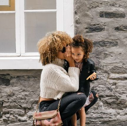 Mutter flüstert kleiner Tochter ins Ohr
