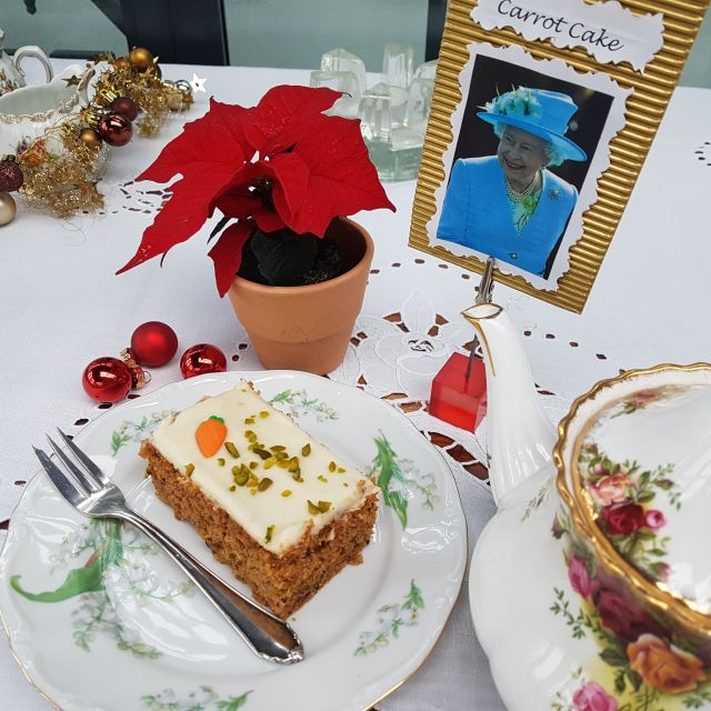 Teller mit Carrot Cake und Teekanne (country roses) und Bild von der Queen.