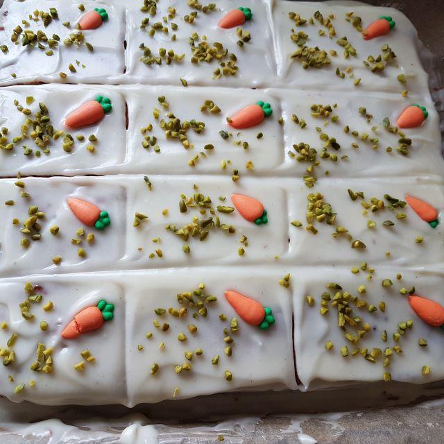 Backblech mit Karottenkuchen, dekoriert mit Pistaziensplitter und Zuckermöhren.
