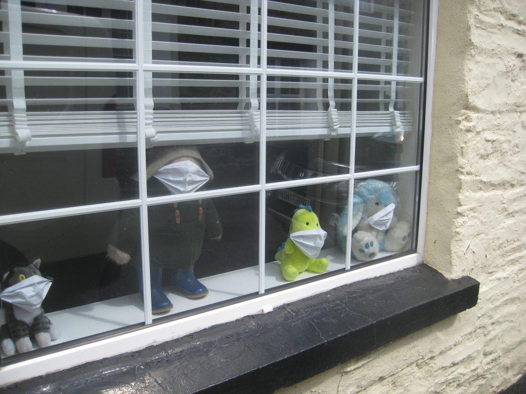Plüschtiere mit Mundschutz im Fenster.