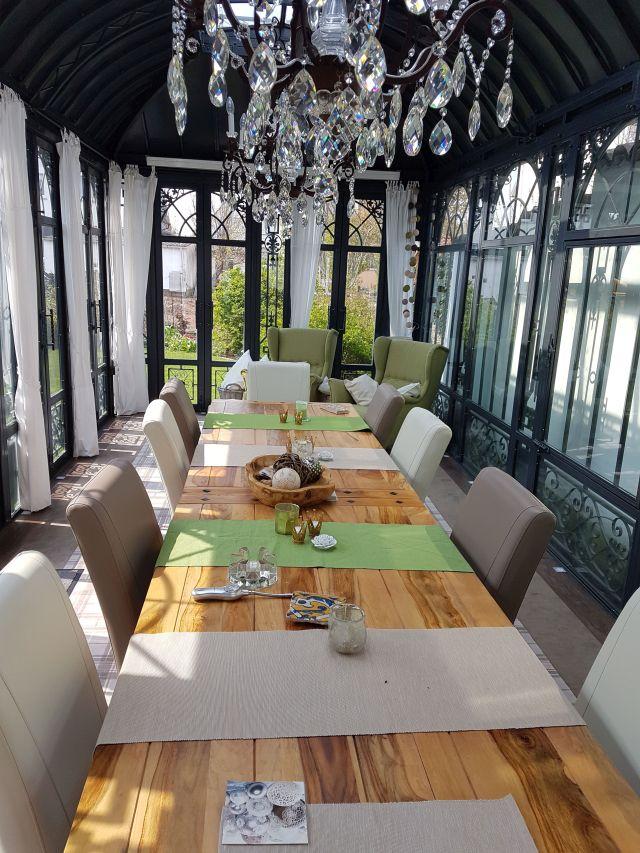 Wintergarten von innen mit Tisch und Sesseln