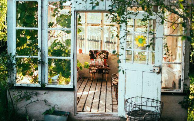 Kleiner Wintergarten oder Conservatory, Blick durch die offene Tür mit geblümtem Sessel im Blickwinkel
