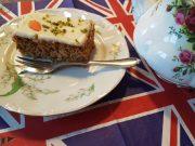 Stück Karottenkuchen auf Teller. Englische Flagge darunter.