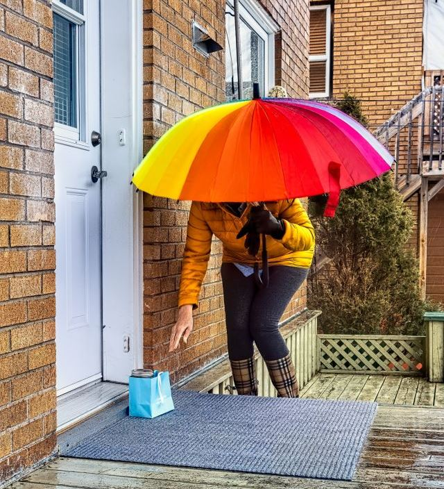 Frau unter buntem Regenschirm und Wellingtons hebt Päckchen  vor der Haustüre auf.