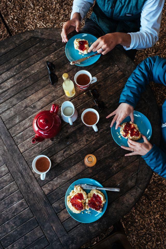 Vogelperspektive, dunkler Holztisch, 3 blaue Teller, Scones mit Clotted Cream und Erdbeermarmelade, 3 Teetassen