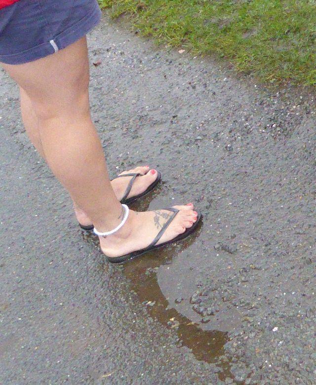 Wetterunempfindlich nackte Frauenbeine und Füße in Flipflops im Regen. Warum frieren Britinnen nicht?