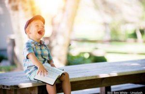 lachender Junge auf Bank mit Buch auf dem Schoß
