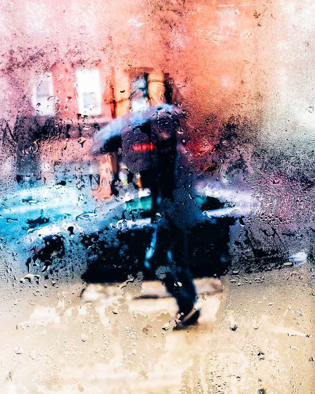 Roadtrip durch Großbritannien, Mann im Regen mit Regenschirm