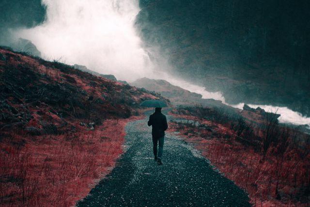 Roadtrip durch Großbritannien, Mann im Regen in Landschaft mit Regenschirm