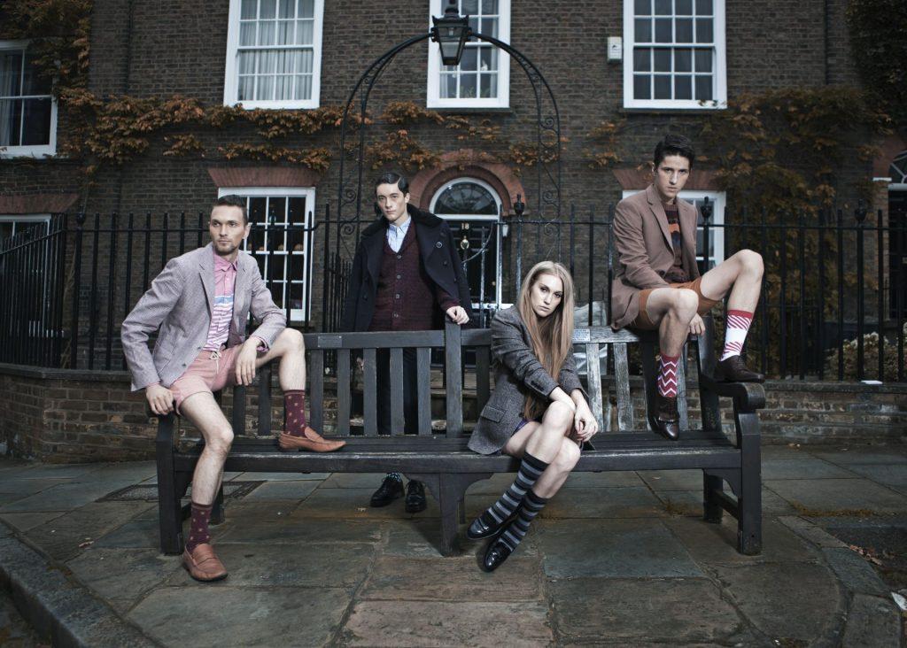3 Männer eine Frau, auf Bank sitzend, Haus im Hintergrund