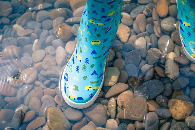 hellblaue Gummistiefel im Wasser mit Kieselsteinen