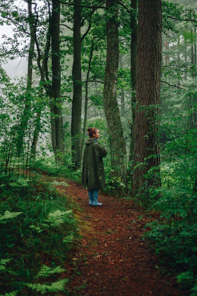 Frau in Regenmantel und Welingtons im Wald