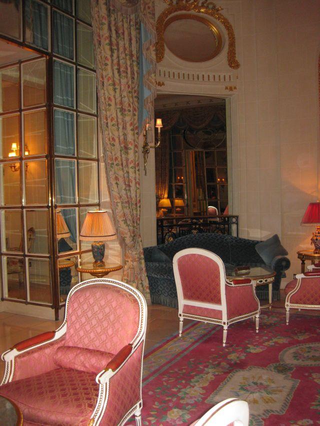 Salon mit roten Sesseln und rotgemustertem Teppich
