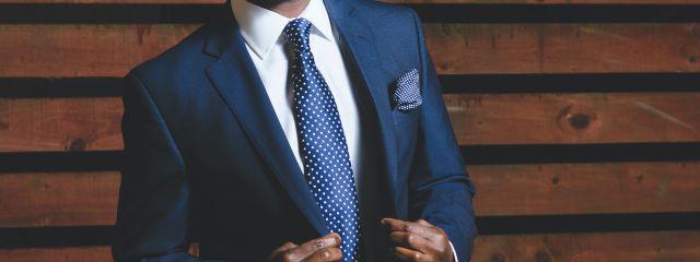 Männeroberkörper im blauen Anzug, weißem Hemd blauer Kravatte