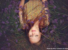 Mädchen verkehrt herum liegend im Lavendelfeld
