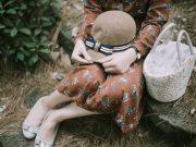 Frauenhände und Hut und Kleid und Beine