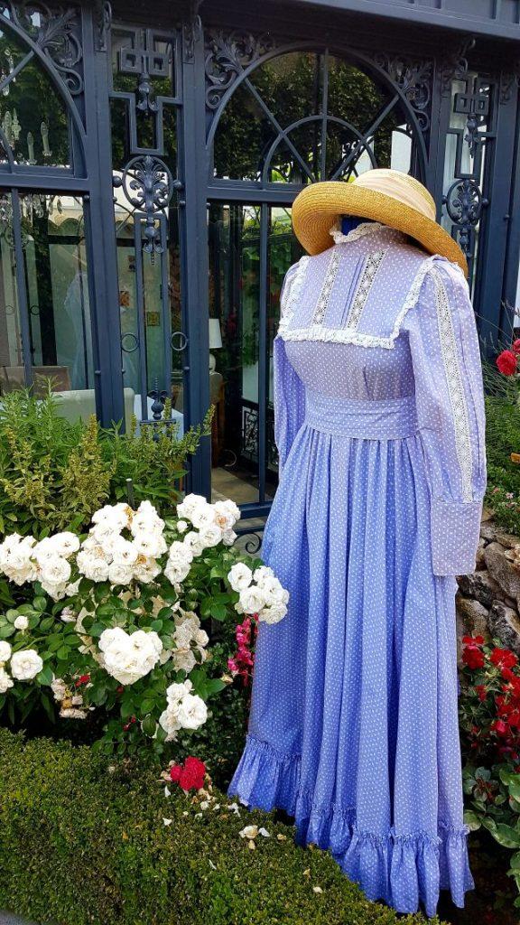 Laura Ashley Kleid im Rosenbeet mit Conservatory im Hintergrund. Laura Ashley dress in rose garden with conservatory in the background.