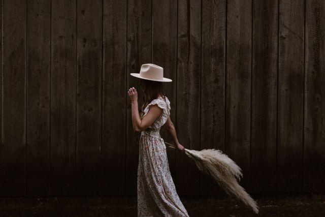 Frau im Blümchenkleid mit hellem Hut und Straßenfedern