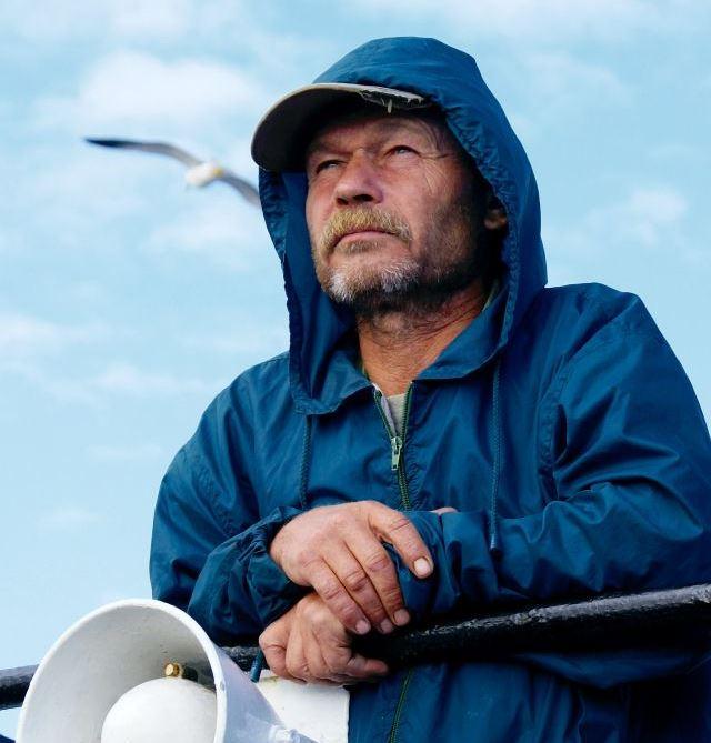 Seemann in blauer Regenjacke mit Kapuze und Megaphon, Shipping Forecast