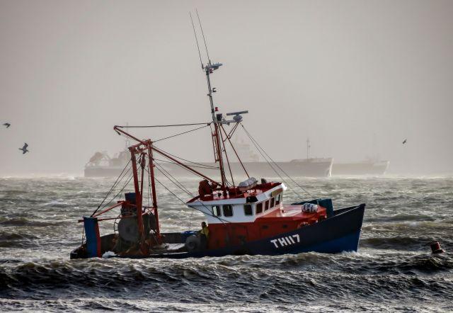Fischkutter rot in hoher See im Hintergrund großer Frachter, shipping forecast